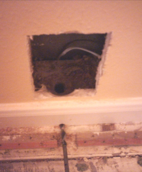 How to: In-Wall Wiring for Your Home Studio-drilling-into-baseboard-.jpg